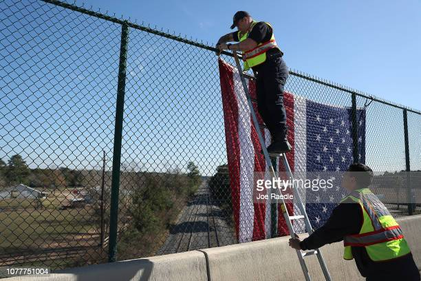 Firefighters Jason Corthell and John Kelley from the Tomball fire department rehearse putting an American flag on an overpass above the rail lines...