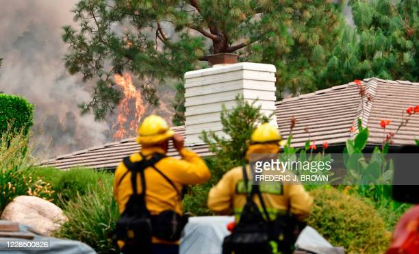 Firefighters keep an eye on the Bobcat Fire as it burns on a hillside behind homes in Arcadia, California on September 13, 2020 which prompted...
