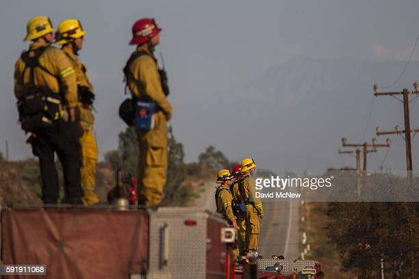 Firefighters keep watch at the Blue Cut Fire on August 18 2016 near Wrightwood California An unknown number of homes and businesses have burned and...