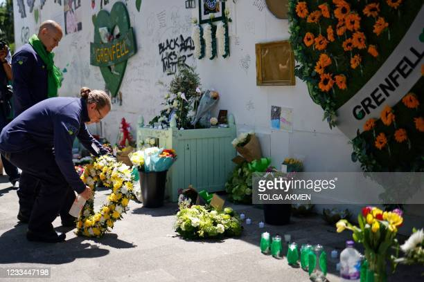 Firefighters lay a wreath as they pay their respects at a memorial to the victims of the Grenfell Tower fire, in west London on June 14 four years...