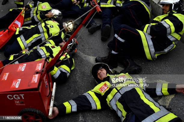Firefighters lay on the ground as they take part in a demonstration to protest against the pension overhauls in Marseille southern France on December...