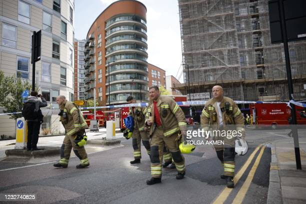 Firefighters leave the scene of a fire at a residential tower block in east London on May 7, 2021. - Over 100 firefighters tackled a blaze that...