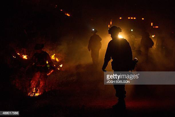 Firefighters light a backfire while battling the Butte fire near San Andreas California on September 12 2015 According to state fire agency CAL FIRE...