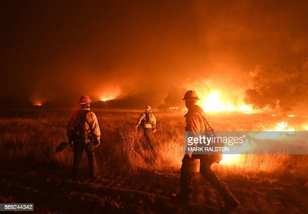 TOPSHOT Firefighters light backfires as they try to contain the Thomas wildfire which continues to burn in Ojai California on December 9 2017 Brutal...