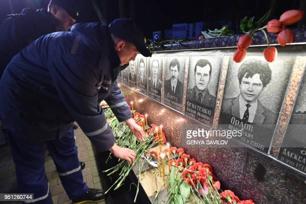 Firefighters light candles and place flowers at the monument to Chernobyl victims in Slavutich the city of the power station's personnel live some 50...