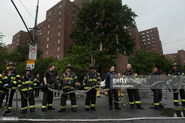Firefighters line up with a hose line after a threealarm fire that broke out at 502 East 14th Street across from Stuyvesant Town in lower Manhattan...