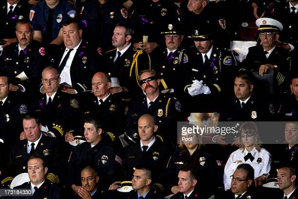 Firefighters listen during a memorial service honoring 19 fallen firefighters at Tim's Toyota Center July 9 2013 in Prescott Valley Arizona The 19...