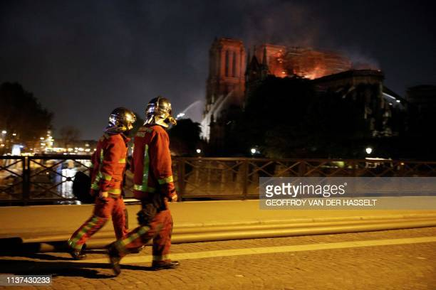 TOPSHOT Firefighters look a fire at the landmark NotreDame Cathedral in central Paris as they cross the Archeveche Bridge on the Seine river on April...