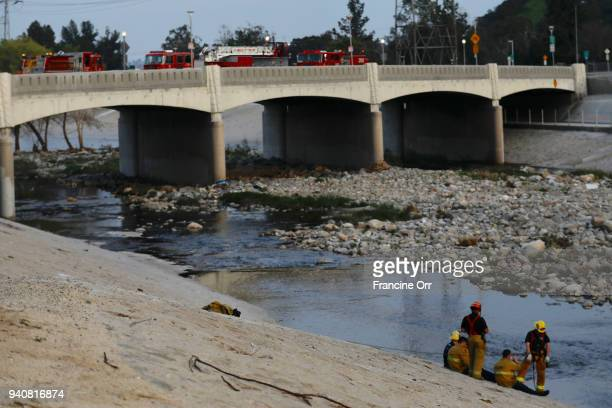 Firefighters look for a 13 year old boy at the LA River near Griffith Park Sunday April 1 The boy was reported to have fallen into a drainage ditch