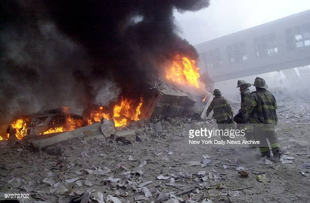 Firefighters look for survivors as they walk through the rubble of the collapsed World Trade Center.,