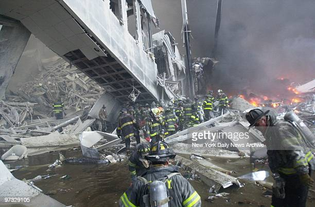 Firefighters look for survivors in the rubble of the World Trade Center after it was struck by a commercial airliner in a terrorist attack. A...