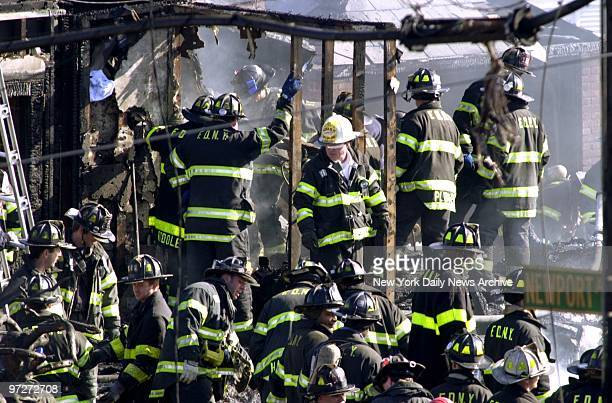 Firefighters look for victims in the smoldering remains of American Airlines flight 587 after it crashed in the Rockaway section of Queens