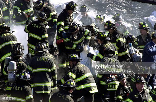 Firefighters look for victims in the smoldering remains of American Airlines flight 587 after it crashed in the Rockaway section of Queens White...