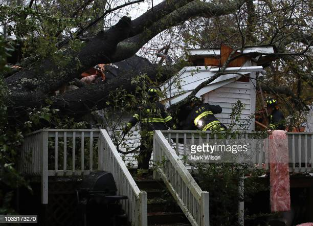 Firefighters look into a home that a large tree fell on that has three people trapped after Hurricane Florence hit the area on September 14 2018 in...
