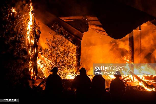 Firefighters look on as a structure burns during the Kincade fire off Highway 128 east of Healdsburg California on October 29 2019 California braced...
