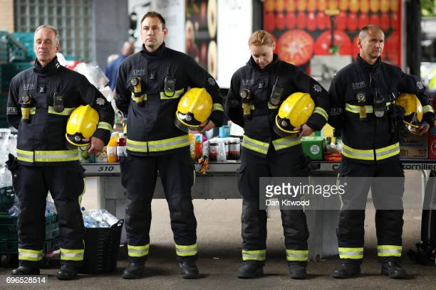 Firefighters look on during a visit by Queen Elizabeth II at the scene of the Grenfell Tower fire on June 16 2017 in London England 17 people have...