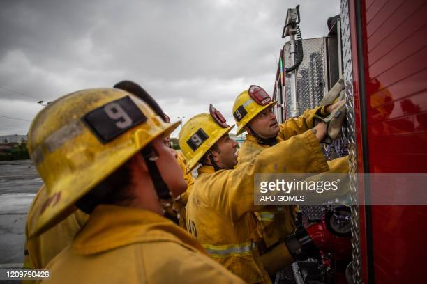 Firefighters look up to fire truck instruments in a morning training session of the LAFD Station No9 team at Skid Row on April 12 2020 in downtown...