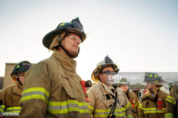 firefighters looking away while standing against clear sky - rescue worker stock pictures, royalty-free photos & images
