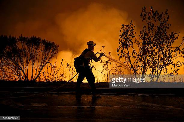 Firefighters make a defensive move on the front lines of the Sherpa Fire to avoid it from moving onto the 101 freeway along Calle Real road on June...