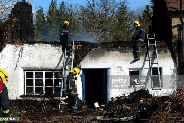 Firefighters make safe the wreckage of film director Ken Russell's home after it was destroyed by fire Monday April 3 2006 The thatched cottage in...
