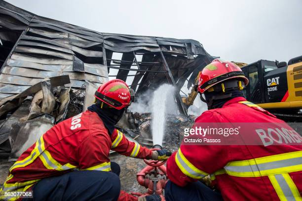 Firefighters make the aftermath of an industrial waste treatment pavilion is burnt in the village of Tondela on October 19 2017 in Viseu Portugal...