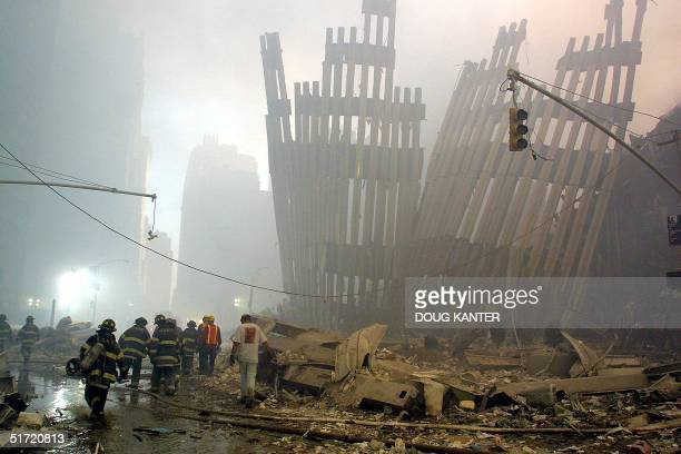 Firefighters make their way through the rubble of the World Trade Center 11 September 2001 in New York after two hijacked planes flew into the...