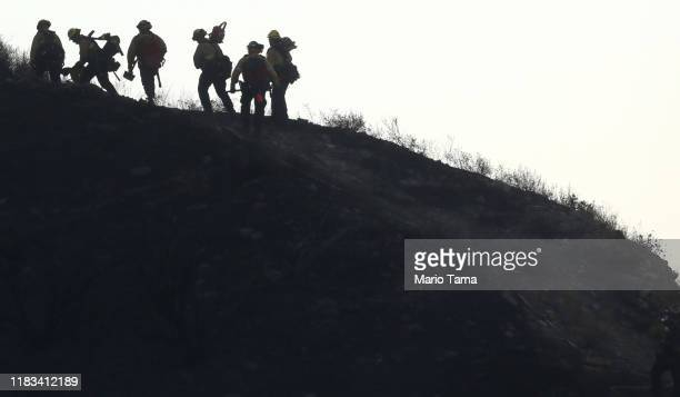 Firefighters make their way up a hillside charred by the Tick Fire on October 25 2019 in Canyon Country California The fire has blackened 4300 acres...