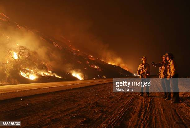 Firefighters monitor a section of the Thomas Fire along the 101 freeway on December 7 2017 north of Ventura California Strong Santa Ana winds are...