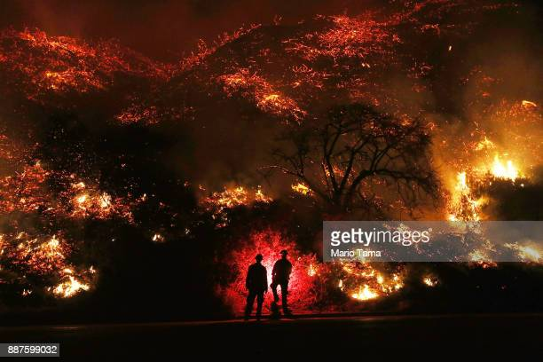 Firefighters monitor a section of the Thomas Fire along the 101 freeway on December 7, 2017 north of Ventura, California. The firefighters...