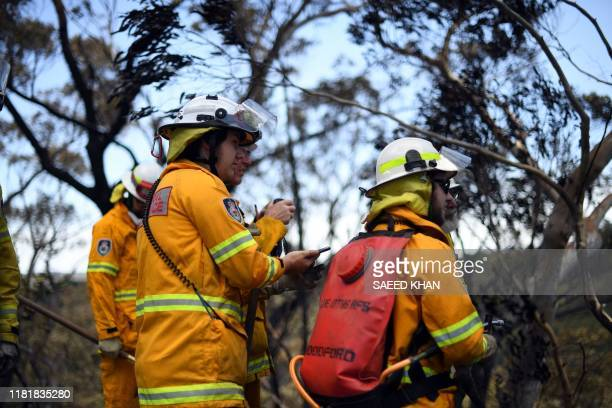 Firefighters monitor bush fires at the Woodford residential area in Blue Mountains on November 12, 2019. - A state of emergency was declared on...