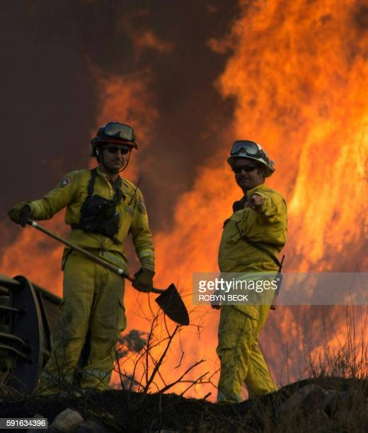 Firefighters monitor the Blue Cut Fire as flames scorch a hillside near Wrightwood California August 17 2016 / AFP / Robyn BECK