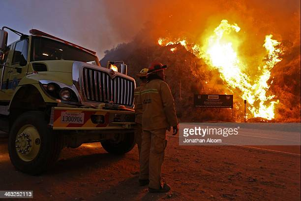 Firefighters monitor the Colby Fire burning for a second day on a hillside on Highway 39 in Azusa California Three men have been arrested and charged...