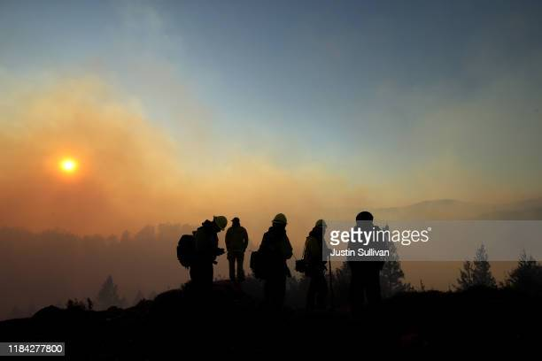 Firefighters monitor the Kincade Fire on October 29 2019 in Healdsburg California Fueled by high winds the Kincade Fire has burned over 76000 acres...