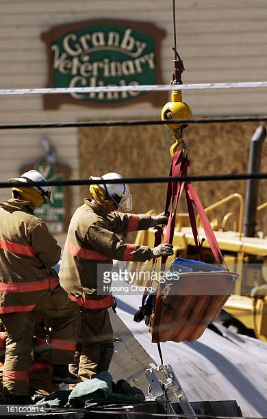 GRANBY CO JUNE 5 2004 Firefighters move the body of Marvin Heemeyer by using a clane from the bulldozer at Gambles store Granby on Saturday morning