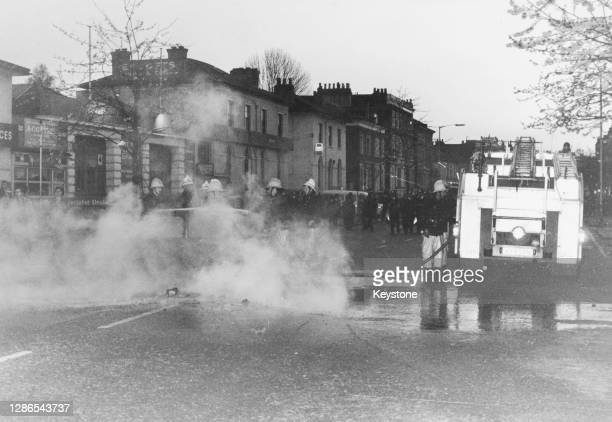 Firefighters of the London Fire Brigade extinguish a fire where a car had been set alight on a night of violence during rioting in Brixton, London,...