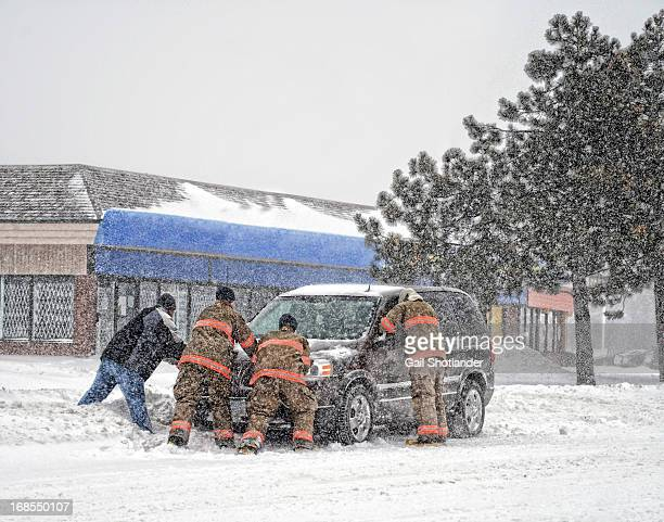 Firefighters offer help to a vehicle and driver. The van is stuck in a snowbank during a snowstorm in February. Location is Brampton. Firemen names...