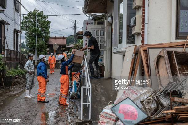 Firefighters offer water to a resident as he cleans his flood-damaged property after torrential rain caused the nearby Kuma River to burst its banks,...