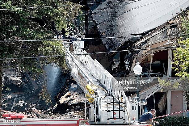 Firefighters on a ladder truck from Montgomery County Fire and Rescue spray water on the stillsmouldering remains of a structure after an overnight...