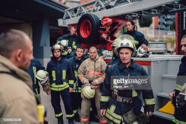 firefighters on team meeting - emergencies and disasters stock pictures, royalty-free photos & images