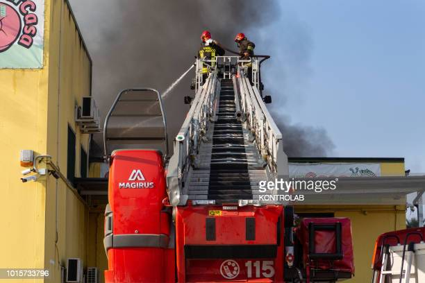 IRENE ROSSANO CALABRIA ITALY Firefighters on the engine ladder during the phases of extinguishing a large fire that destroyed a shed with Cash and...