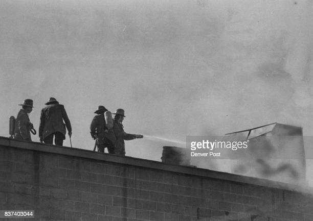 Firefighters On The Job Firemen battle a fire that did heavy damage Monday to a cinderblock building at 3819 Inca St The building houses the Howco...
