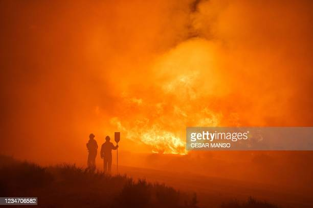 Firefighters operate at the site of a wildfire between Navalacruz and Riofrio near Avila, central Spain, on August 16, 2021. - A thousand people were...