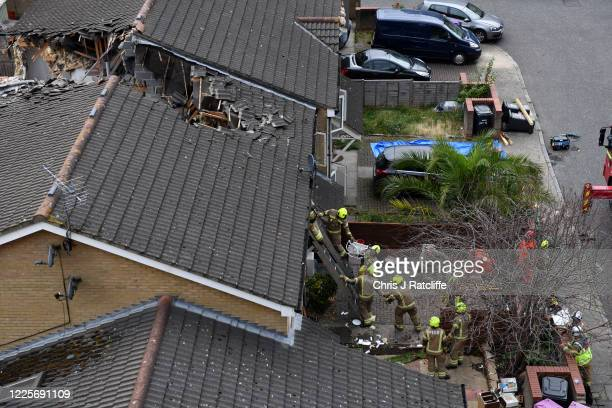 Firefighters pass a seat and a cushion down as they gain entry to a terraced house through a window on the top floor after a 20metre crane collapsed...