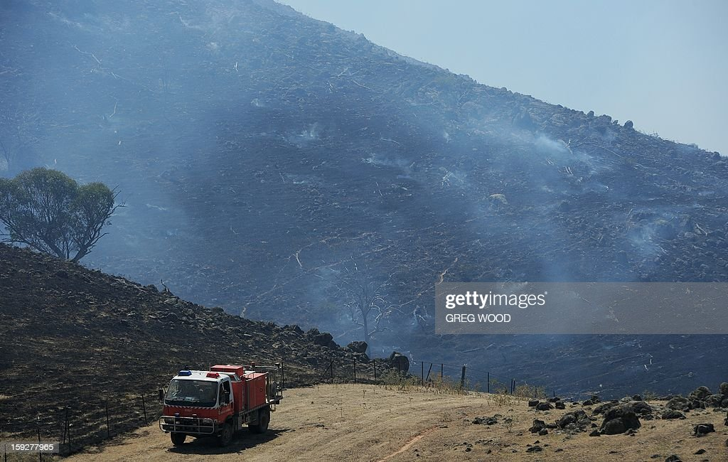 Firefighters patrol the edge of a scrubfire as it burns up a hillside south of Bookham, near Yass in the southern region of Australia's New South Wales state, on January 11, 2013. After two days of cooler weather, heat and high winds returned to much of the country as fire crews tackled the infernos that have been burning for a week, 18 of them out of control in the most populous state of New South Wales. AFP PHOTO / Greg WOOD