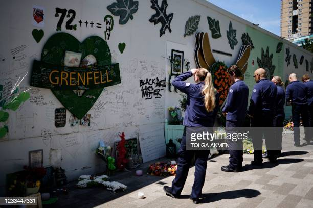 Firefighters pay their respects at a memorial to the victims of the Grenfell Tower fire, in west London on June 14 four years after the fire in the...