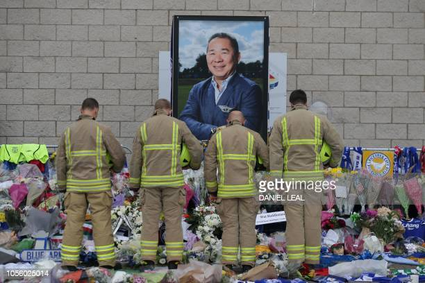 TOPSHOT Firefighters pay their respects in front of a portrait of Leicester City Football Club's Thai chairman Vichai Srivaddhanaprabha among the...