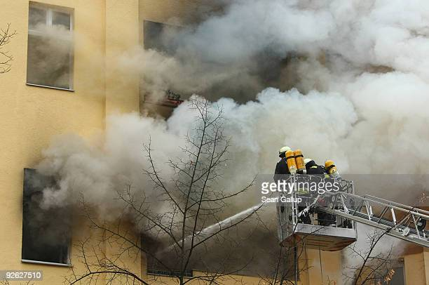 Firefighters perched on a ladder shoot water into a blaze in a secondstorey apartment on November 3 2009 in Berlin Germany The fire occured in an...