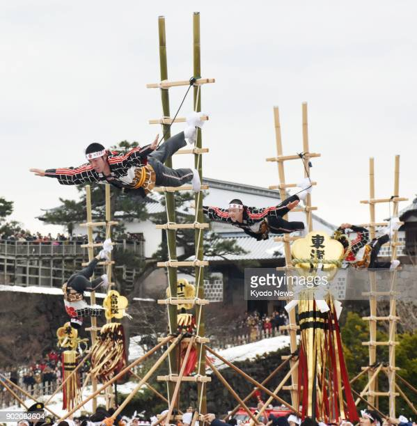 Firefighters perform 'Kaga Tobi' acrobatic stunts on sixmeter ladders dating from the Edo period during an annual New Year's ceremony at Kanazawa...
