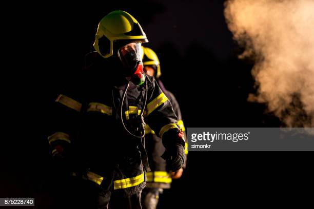 firefighters - fire protection suit stock photos and pictures