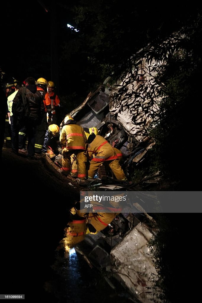 Firefighters, police officers and rescuers help in the accident site after a bus driver apparently lost control in Tome, in Biobio province, some 500 km south of Santiago, on February 9,2013. At least 15 people were killed and 19 others were injured when the bus full of passengers fell into a ravine in central Chile, a local official said.
